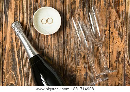 Champagne Bottle, Two Empty Champagne Glasses And Two Wedding Rings On Wooden Background, Love Conce