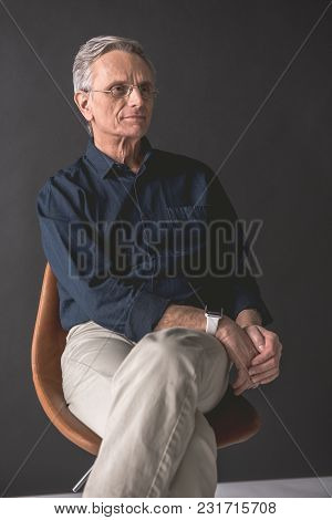 Portrait Of Pensive Old Businessman Having Rest On Comfortable Chair. Contemplative Employer Concept
