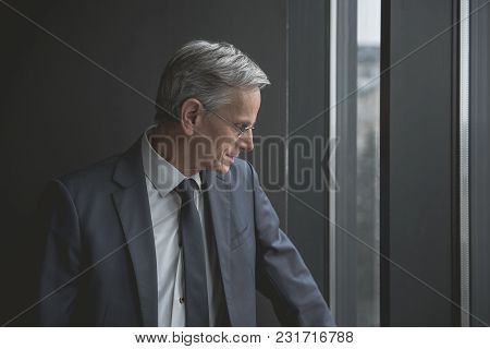 Side View Smiling Old Businessman Looking At Window While Standing In Room. Job And Rest Concept