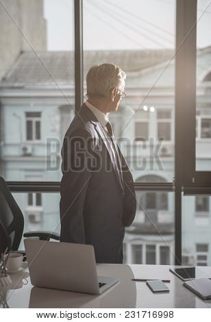 Side View Pensive Retire Businessman Looking At Window While Standing Near It In Office. Reverie Dur