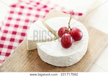 Cheese Wheel With A Piece Of Cheese On A Wooden Board With Fruits And Red Checkered Tablecloth. Came