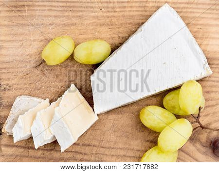 Cheese Board. Creamy Brie On Rustic  Cutting Board Over White Wooden Background, Top View. Camembert