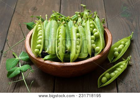 Pods Of Green Peas In Wooden Bowl, Close Up View