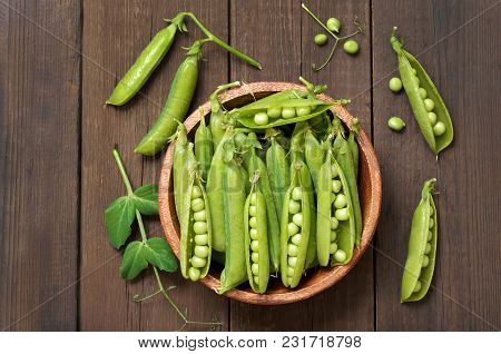 Pods Of Green Peas In Wooden Bowl On A Wooden Background, Top View