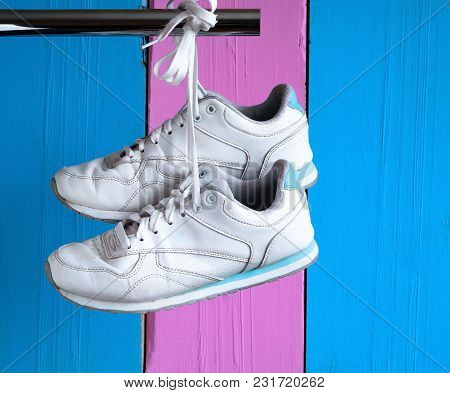 Sports Shoes On A Gentle Background Of Two Colors, Hanging On A Metal Pipe, Space For Text,