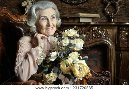 Portrait Of Senior Woman With Flowers At Home