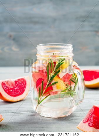 Infused Detox Water With Grapefruit And Rosemary In Mason Jar On Gray Wooden Table. Diet Healthy Eat