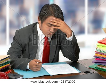 Employee Reading Documents At His Desk