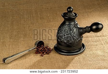 A Steel Measuring Spoon With Roasted Coffee Beans And A Made Of Black Clay сoffeepot On A Coarse Can