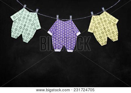 Baby Boy Clothing On Clothesline On Blackboard Background