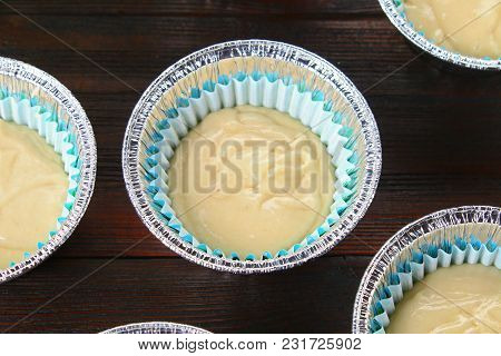 Dough In Molds For Muffins On A Wooden Table
