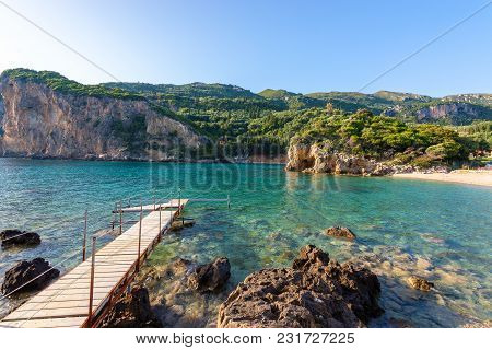 Wooden Pier In Paleokastritsa Bay With Sand And Crystal Sea Water. Corfu Island, Greece.