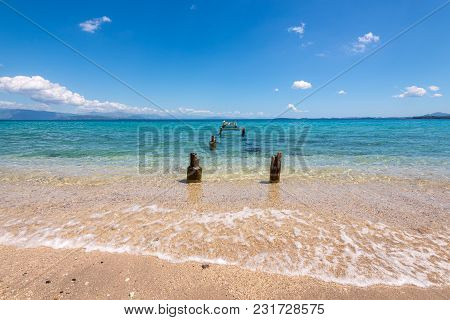 Old Wooden Pier And Crystal Turquoise Water On Corfu Island. Ipsos Village, Greece.