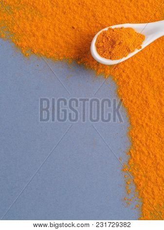 Turmeric Powder Or Curcuma Longa And White Spoon With Turmeric Powder On Gray Background. Top View.