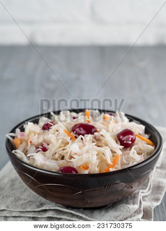 Traditional Russian Appetizer Sauerkraut With Cranberry And Carrot In Dark Craft Plate On Gray Rusti