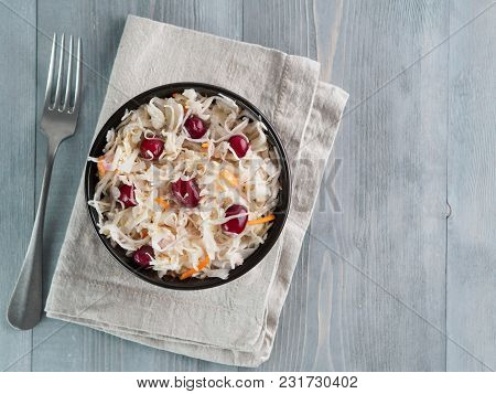 Traditional Russian Appetizer Sauerkraut With Cranberry And Carrot In Dark Craft Bowl On Gray Wooden