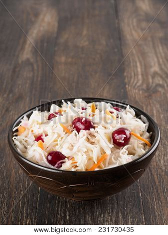 Traditional Russian Appetizer Sauerkraut With Cranberry And Carrot In Dark Craft Plate On Brown Rust