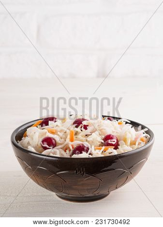 Traditional Russian Appetizer Sauerkraut With Cranberry And Carrot In Dark Craft Plate On White Wood
