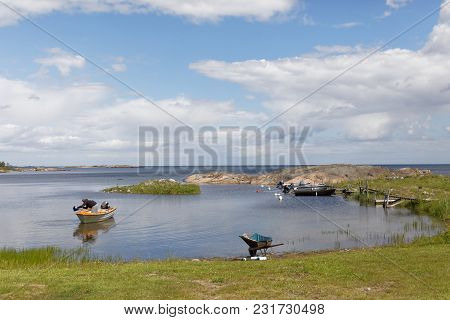 Vaddo, Sweden - June 25, 2017: Swedish Archipelago And A Small Harbor With Boats And A Man Preparing