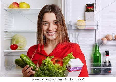 Cheerful Lovely Young Woman With Attractive Look Has Broad Smile, Poses Near Fridge With Fresh Veget