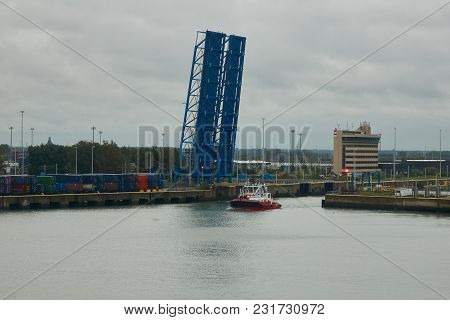 Canal Lift Bridge In An Elevated Position In The Seaport Of Zeebrugge. The Ship Is Passing By.