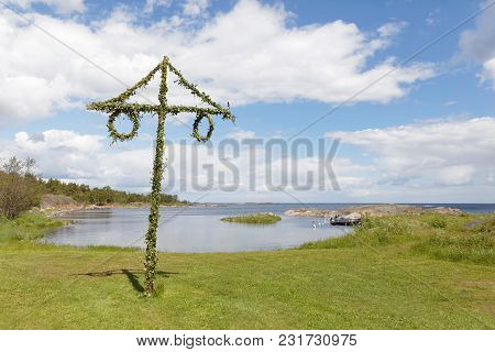Tiny Maypole In The Swedish Archipelago, Blue Sky And White Clouds In The Background