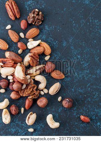 Background Of Nuts - Cashew, Pecan, Pine Nuts, Hazelnuts - On Dark Blue Background With Copy Space.