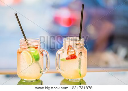 Strawberry Mint And Lemon With Straws Lemonade In Glass Goblet On Blurred City Background