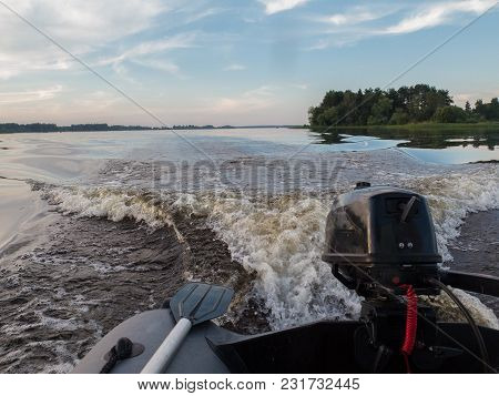 A Motor Boat Sails Along The River. Fishing At Sunset.