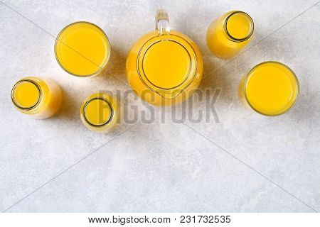 Glass Bottles, Glasses And A Pitcher Of Fresh Orange Juice With Slices Of Orange And Yellow Tubes On