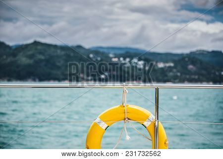 Close-up Yellow Life Ring Hanging On Boat With Ocean Background