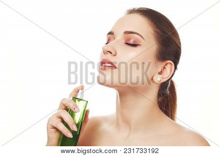 Portrait Of Pleased Adorable Woman With Wonderful Make Up, Uses Her Favourite Parfume, Looks Beautif