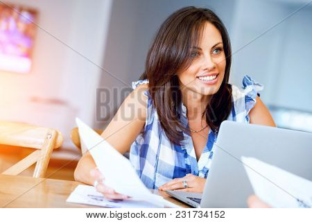 Woman with papers in their living room