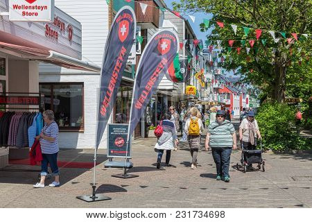 Helgoland, Germany - May 22, 2017: Shopping People In Main Street Of Helgoland With Many Billboards.