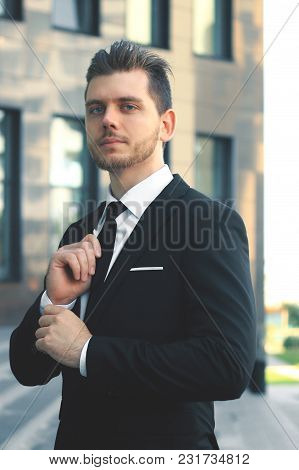 Businessman Adjusting His Tie At The Entrance To The Office Building.