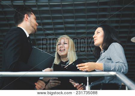 Close Up.group Of Business People Talking On The Balcony Of The Office.