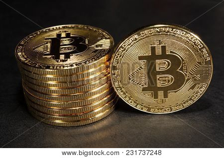 Column Of Bitcoins With One Single Coin Next To Them On Dark Leather Surface. Virtual Crypto Currenc