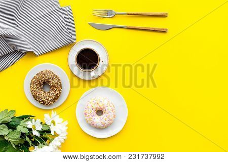 Holiday Lunch For Woman With Cup Of Americano, Donut And Flowers On Yellow Table Background Top View