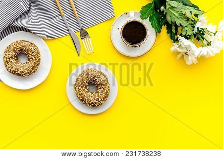 Woman Desk With Flowers, Coffee And Donuts For Breakfast In Spring Desing On Yellow Background Flat