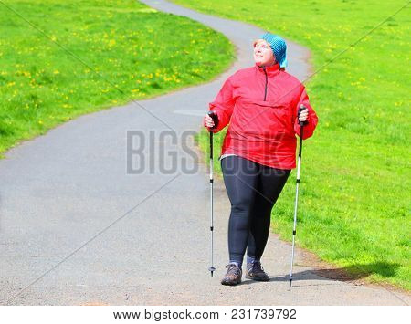 Happy overweight woman slimming and enjoying life on spring meadows. Healthy lifestyle concept.