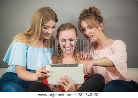 Women Sitting On Sofa Having Fun Surfing On The Internet Using Smart Digital Pc Tablet Modern Device