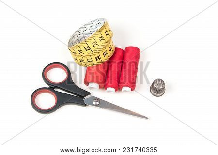 Sewing Accessories And Tools. Red Sewing Threads, Black Scissors, Yellow Measuring Tape And Thimble