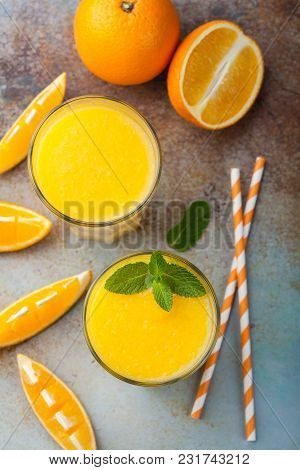 Two Glasses With Freshly Squeezed Orange Juice And Mint On An Old Rusty Blue Background. Top View.