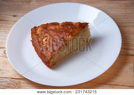 Fresh Homemade Apple Pie With A Flakey Crust On White Plate And Wooden Table