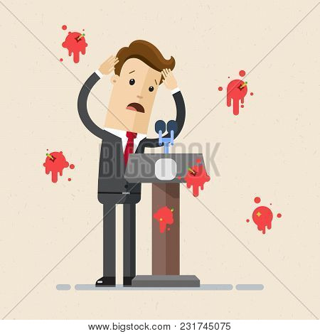 A Man In A Suit, Business Man, Stands Behind A Rostrum With A Microphone, Having Tomatoes Thrown At