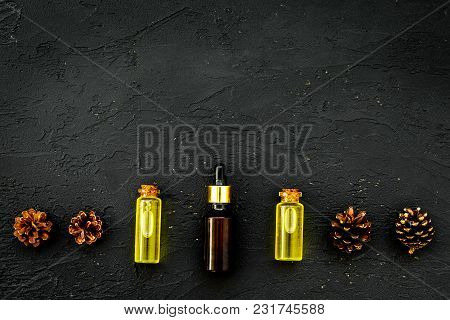 Natural Spa Cosmetics With Pine Essential Oil For Aroma On Black Desk Background Top View Mock-up