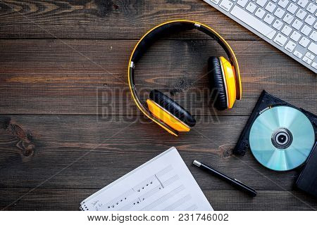 Work Desk Of Modern Composer. Music Notes Near Headphones On Wooden Background Top View.