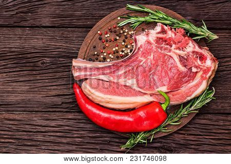 Top View Raw Beef Steak On Wooden Cutting Board With Red Chili Pepper And Rosemary. Selective Focus