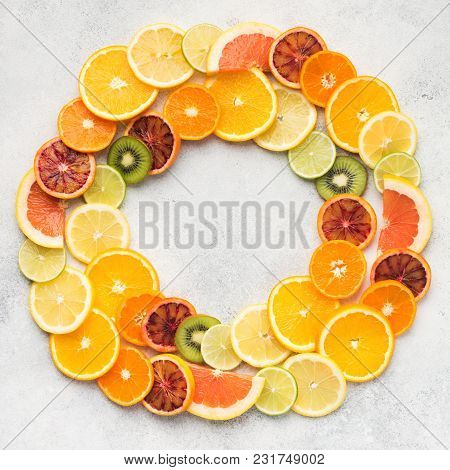 Different Varieties Of Citrus Fruits And Kiwis Arranged In A Circle Frame On White Table, Top View,