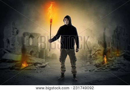 Destroyed place after a catastrophe with man and  burning flambeau concept